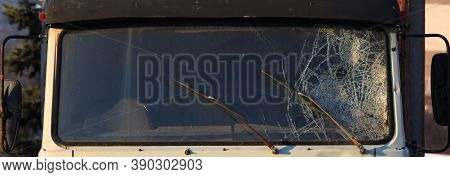 Broken Windshield Of A Truck (lorry). Accident And Traffic Accident. The Crash. A Gunshot Attack On