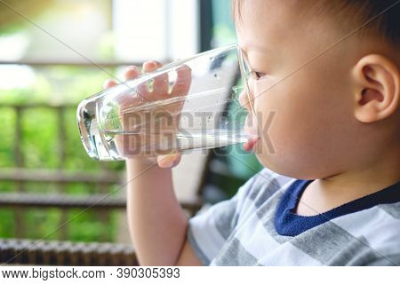 Cute Thirsty Little Asian 2 Years Old Toddler Baby Boy Child Holding And Drinking Glass Of Water By