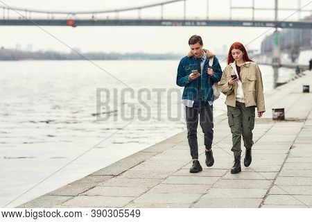 Full Length Shot Of Two Teenagers Totally Absorbed In Smartphones, Ignoring Each Other While Walking