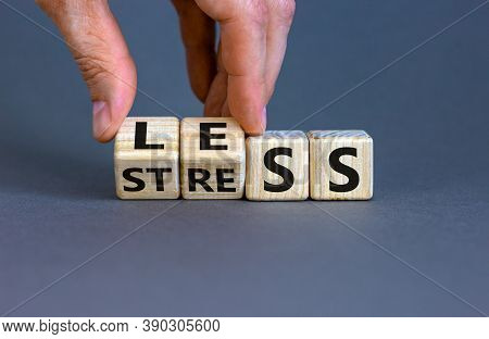 Having Less Stress Or Being Stress-less. The Word 'stress' And 'less' On Wooden Cubes. Male Hand.  B