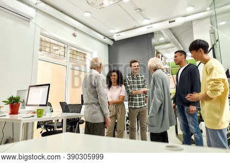 Cheerful Young Team Greeting New Employees, Aged Man And Woman, Senior Interns Shaking Hands With Co