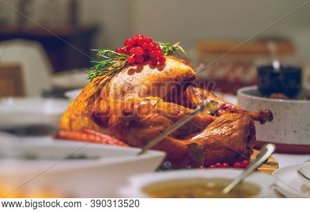 Tasty Fried Turkey in the Center of the Table for Thanksgiving Day. Festive Dinner at Home. Traditional American Holiday.
