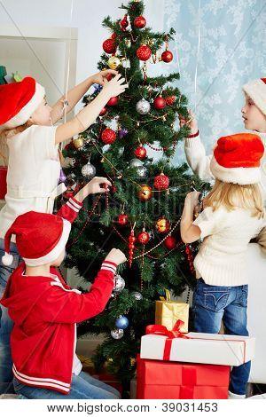 Group of adorable kids in Santa caps decorating xmas tree