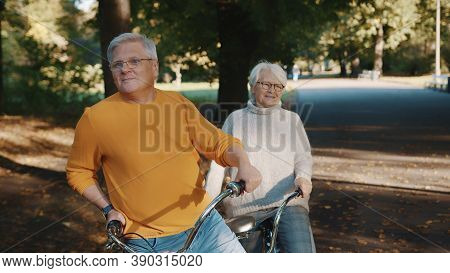 Senior Couple Riding Double Bicycle In Autumn. Grandmother And Grandfather Cycling Together . Elderl