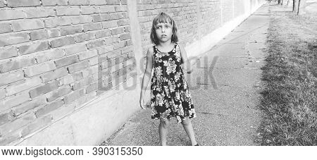 Girl Scared. Halloween Theme. A Child In A Dress With Flowers Against A Brick Wall Is Afraid. The Gi