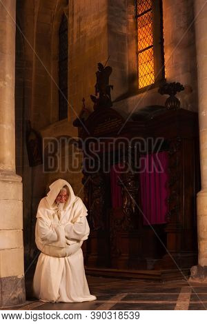 Praying monk kneeling on the floor of a medieval church