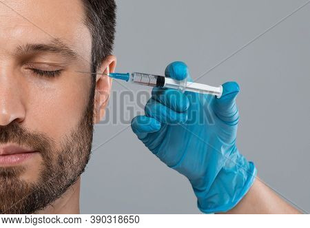 Closeup Of Middle-aged Man Getting Anti-aging Injection In Eye Zone At Clinic Or Salon, Copy Space.
