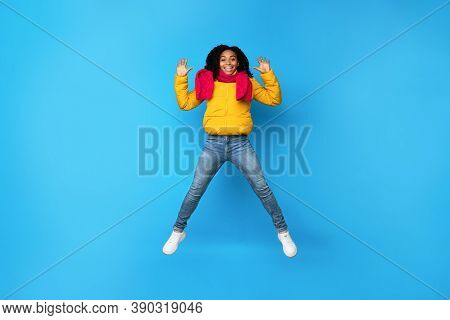 Hello. Joyful African American Woman Jumping Waving Hands In Mid-air And Smiling To Camera Posing We