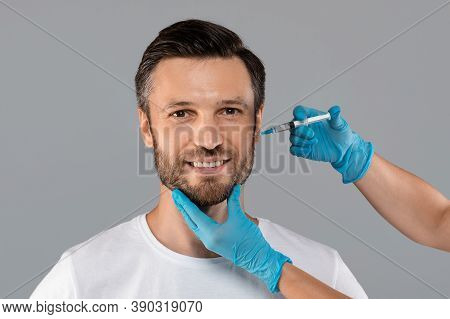 Cosmetician In Protective Gloves Injecting Face Filler For Middle-aged Man Over Grey Studio Backgrou