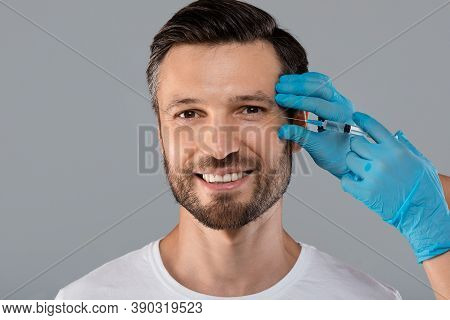 Happy Middle-aged Man Getting Anti-wrinkle Injection In Eye Zone Over Grey Studio Background. Cosmet
