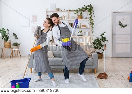 Great House Cleaning Together And Rock Band. Cheerful Husband Plays On Broom, Wife In Apron Sings In