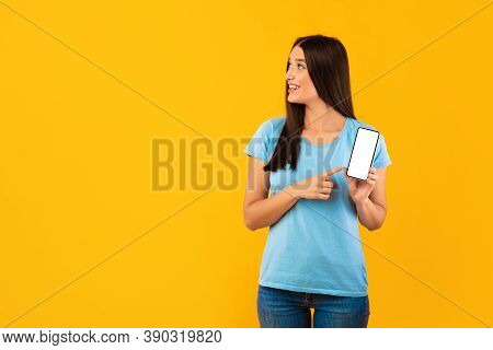 Look At It. Portrait Of Woman Holding And Pointing At White Blank Cell Phone Screen Over Yellow Stud