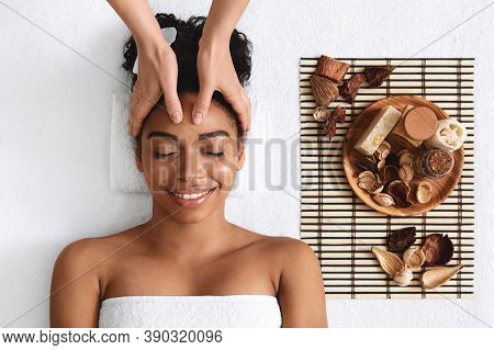 Smiling Black Lady Having Aromatherapy Session At Spa, Top View, White Background. Cheerful African