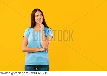 Pensive Displeased Young Woman Thinking About Question, Touching Chin And Looking Away At Copy Space