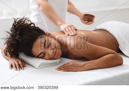 Spa Therapist Applying Exfoliating Body Mask On Sleeping Black Woman Back At Luxury Spa, Body Care C