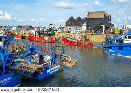 Whitstable Harbour, Kent, England - Oct 14 2020: Colourful Fishing Boats And Trawlers On A Bright, S