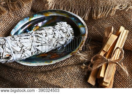 An Image Of White Sage Smudge Sticks In An Abalone Shell With A Burlap Background.