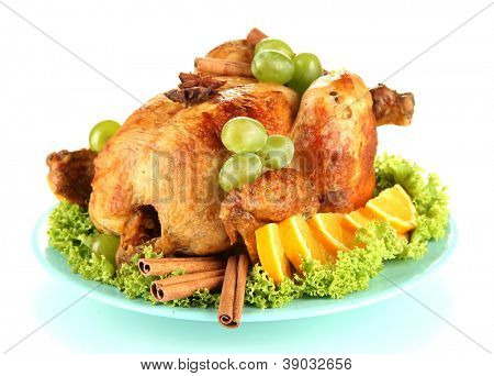 whole roasted chicken with lettuce, grapes, oranges and spices on blue plate isolated on white