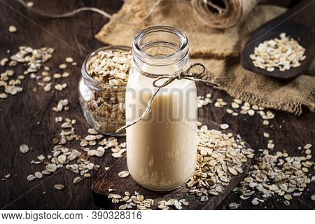 Oat Flakes Milk, Non Dairy Alternative Plant Based Drink In Glass, Wooden Rustic Kitchen Table, Copy