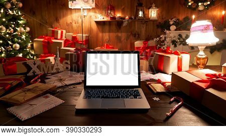 Laptop Computer With White Blank Empty Mock Up Screen On Merry Christmas Table With Presents Gifts,