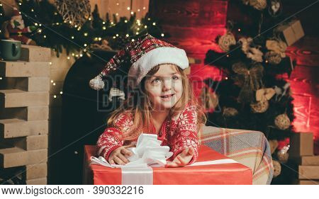 Happy Christmas Little Girl With A Big Christmas Present. Cheerful Cute Child Opening A Christmas Pr