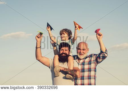Grandfather With Son And Grandson Having Fun In Park. Happy Child Playing With Toy Paper Airplane Ag