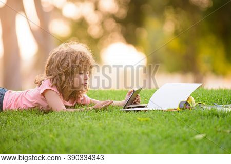Child Studies And Learn With Tablet Outside. Funny School Child Schoolboy Lies On Grass. Distance Le