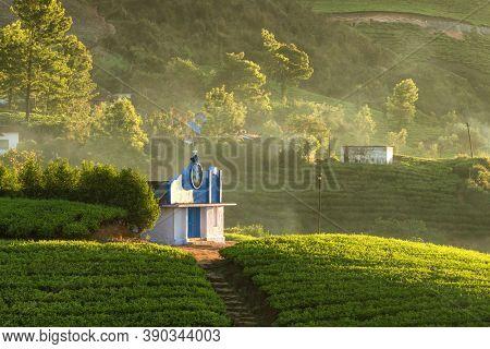 Small christian chapel in beautiful tea plantations in Munnar, Kerala, India. Beautiful rural tea plantations landscape at sunrise