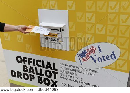 IRVINE, CALIFORNIA - 18 OCT 2020: Woman placing mail in ballot in an Official Ballot Drop Box in Orange County, California.