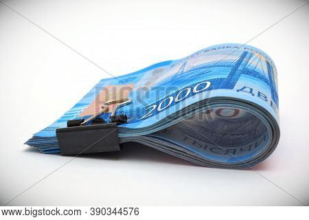 Russian Money. A Bundle Of 2000 Rubles Bills Is Tied With An Office Clip And Lies On A White Surface