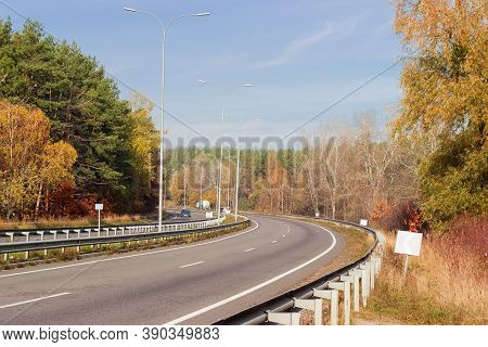 Section Of The Motorway With Bend, Road Surface Marking, Lampposts, Traffic Barriers And Forest On B