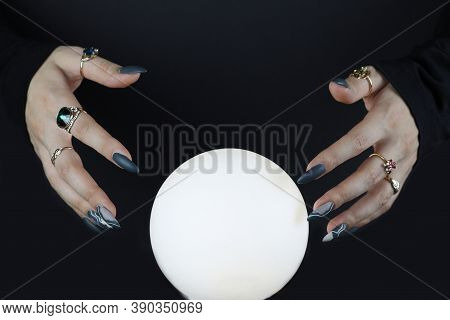 Clairvoyance And Divination. Women's Hands Reach For A Crystal Magic Ball. Predicting The Future.