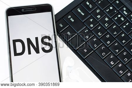 Dns - Acronym Domain Name System Is An Inscription On The Phone Screen That Lies On The Laptop Keybo
