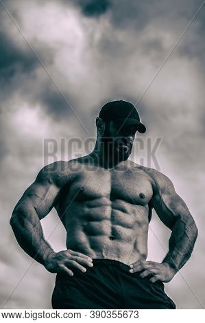 Strong Young Sport Bearded Man With Perfect Athlete Physique Body On Cloudy Sky Background