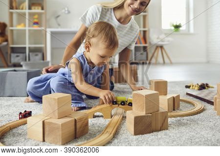 Young Nanny And Toddler Boy Playing With Wooden Blocks In Modern Cozy Nursery Room