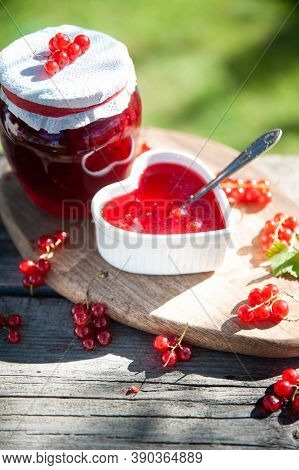 Red, Juicy Berries Of Red Currants And Jars Of Berry Jam On A Wooden Table, On A Green Background Of