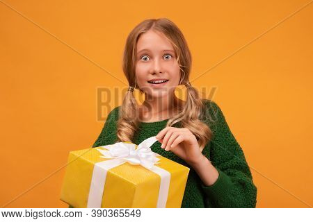 Image Of Charming Blonde Girl 12-14 Years Old In Warm Green Sweater Smiling And Holding Present Box