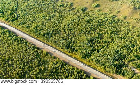 Aerial Flying Over A Rural Road With Two Cars Driving Opposite Each Other On The Lane Between Forest