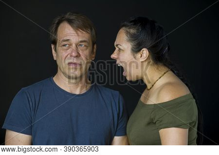 A Woman Yells At A Man On A Dark Neutral Background.the Concept:family Quarrel, Conflict Between Peo