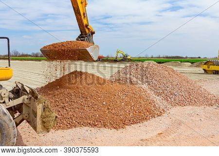 Excavator Is Catching Fraction, Small Crushed Stone, With His Front Bucket From Pile At Building Sit