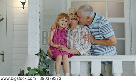 Happy Senior Grandparents Couple With Granddaughter Smiling In Porch At Home. Lovely Grandfather And