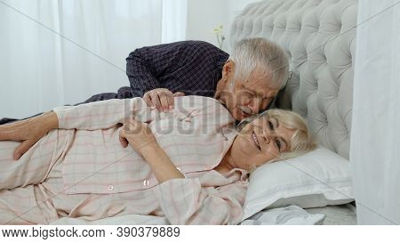 Senior Caucasian Grandparents Couple Lying In Bed At Home In Morning. Man Gently Whispering To Woman