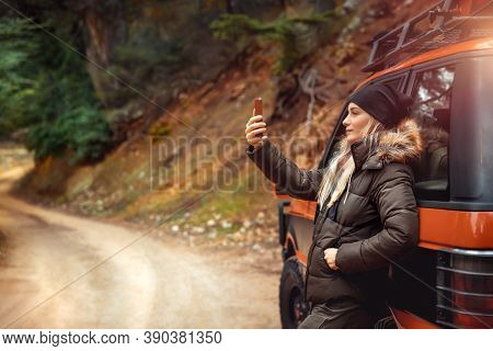 Pretty woman taking a selfie using a smartphone, enjoying a car road trip along the mountainous forest, off-road trip, active people lifestyle