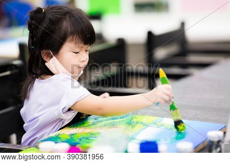 Soft Focus. Cute Asian Girl Is Coloring On A Canvas. Child Grab A Large Paintbrush, Paint And Make A
