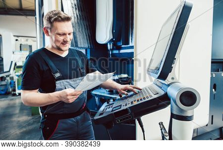 Worker in industrial workshop programming a cnc machine using keyboard