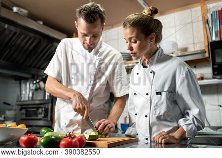 Young professional chef with knife showing his female trainee how to cook fresh zucchini while both standing by table in kitchen of restaurant