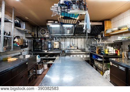Interior of large kitchen of modern luxurious restaurant including big long table for cooking, kitchenware, sink, shelves, electric stove and oven