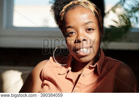 Young cheerful restful woman of African ethnicity looking at you with toothy smile while sitting by window in home environemnt