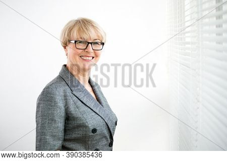 Portrait of successful mature business woman looking at camera against a window in an office.