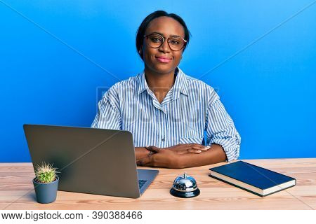 Young african woman working at hotel reception using laptop relaxed with serious expression on face. simple and natural looking at the camera.